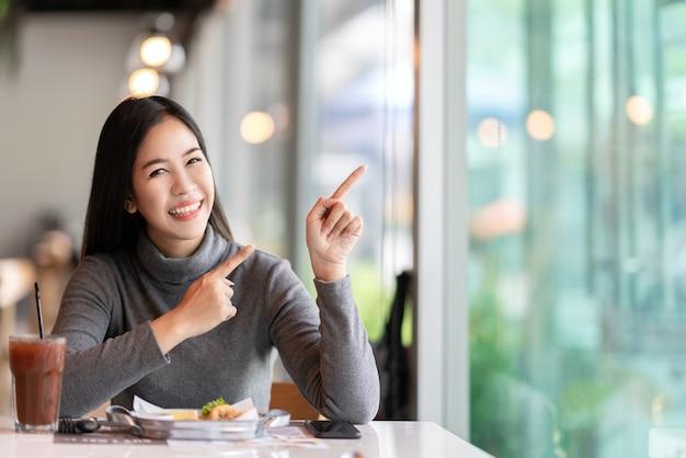Jonge aantrekkelijke aziatische vrouw die aan kant voor het tonen van bericht richt
