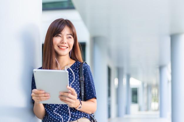 Jonge aantrekkelijke aziatische vrouw die buiten haar kantoor naar muziek luistert vanaf haar computertablet