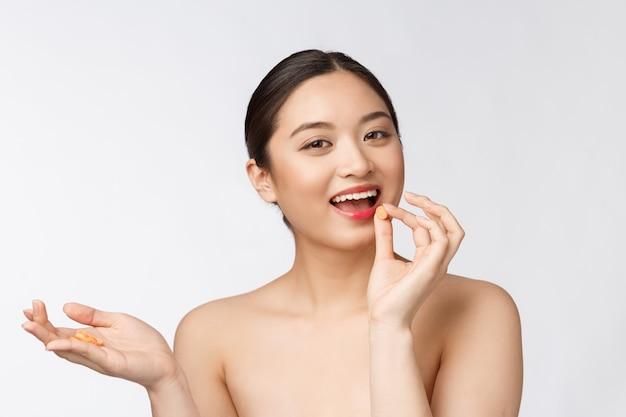 Jonge aantrekkelijke aziatische vrouw die een over geïsoleerde capsule of een pil neemt