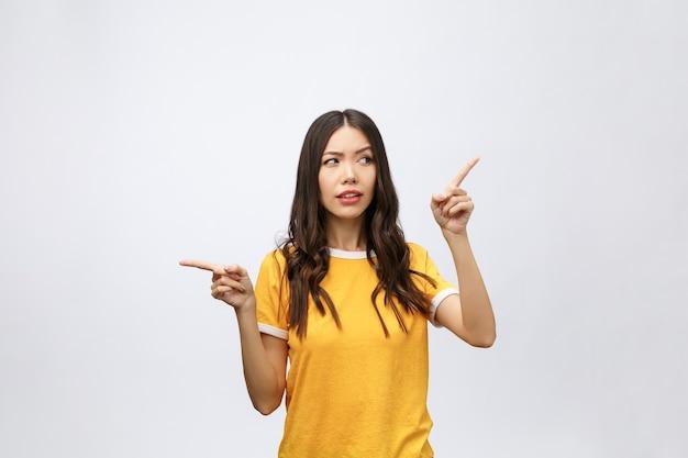 Jonge aantrekkelijke aziatische vrouw die met ongelukkige emotie naar de vinger wijst