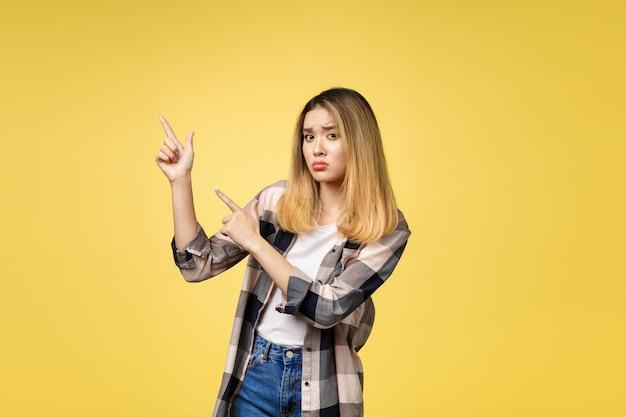 Jonge aantrekkelijke aziatische vrouw die naar de vinger met ongelukkige emotie wijst.