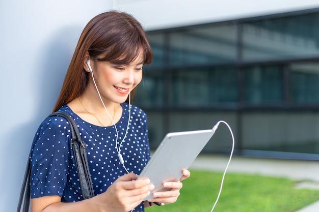 Jonge aantrekkelijke aziatische vrouw die op het nieuws op haar moderne technologieconcept van de computertablet let