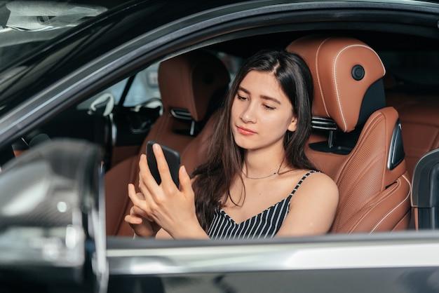 Jonge aantrekkelijke aziatische vrouw die telefoon gebruikt terwijl ze in een luxe auto aan zee zit