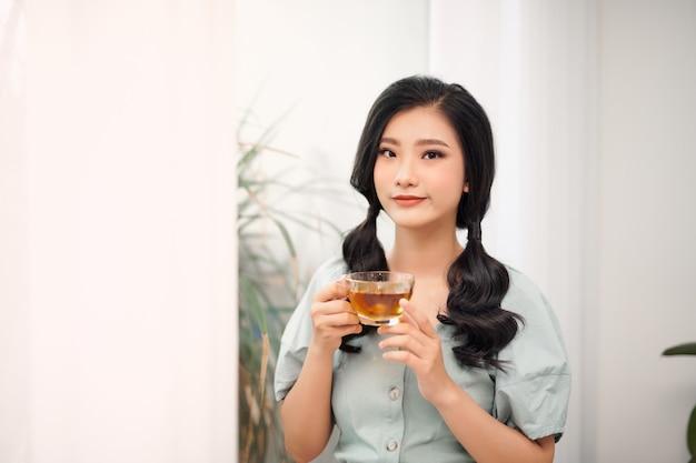 Jonge aantrekkelijke aziatische vrouw die thee drinkt