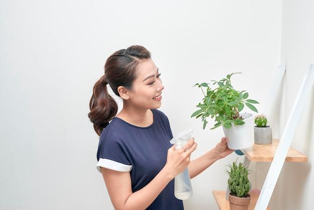 Jonge aantrekkelijke aziatische vrouw die water geeft aan een plant