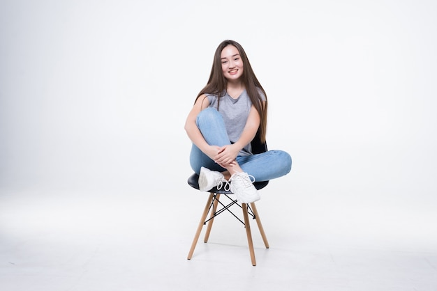 Jonge aantrekkelijke aziatische vrouwenzitting op de stoel die op witte muur wordt geïsoleerd