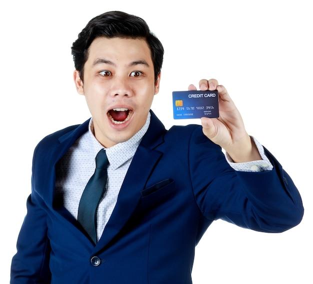 Jonge aantrekkelijke aziatische zakenman die een marineblauw pak met wit overhemd en stropdas draagt en zijn blauwe creditcard omhoog houdt en een verrassingsgezicht doet op een witte achtergrond. geïsoleerd