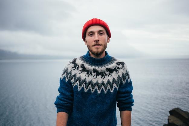Jonge aantrekkelijke bebaarde duizendjarige man in rode visser of zeeman beanie hoed en traditionele ijslandse ornament blauwe trui