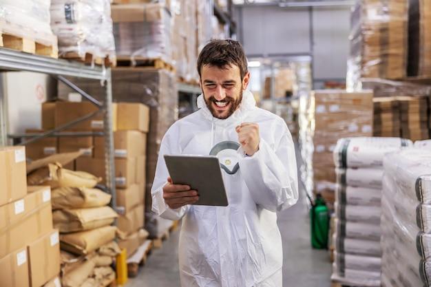 Jonge aantrekkelijke bebaarde lachende supervisor in beschermende uniform staande in magazijn