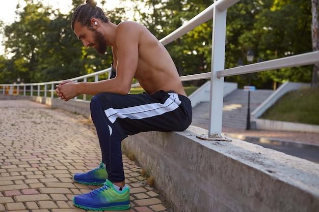 Jonge aantrekkelijke bebaarde man heeft extreme sporten in het park, rust in het park na het joggen.