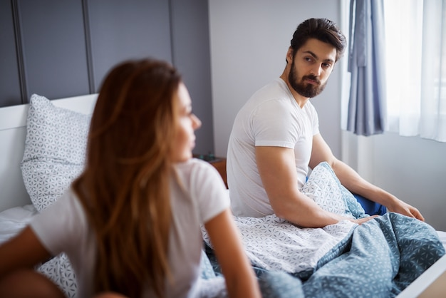Jonge aantrekkelijke bebaarde man kijken naar zijn ongelukkige vriendin of vrouw zittend aan de andere kant van het bed thuis of hotel.