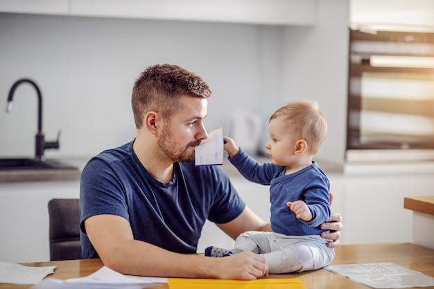 Jonge aantrekkelijke bebaarde vader zit aan de eettafel en speelt met zijn zoon. hij houdt de rekening in zijn mond. zoon zit op tafel en probeert hem te helpen met financiën.