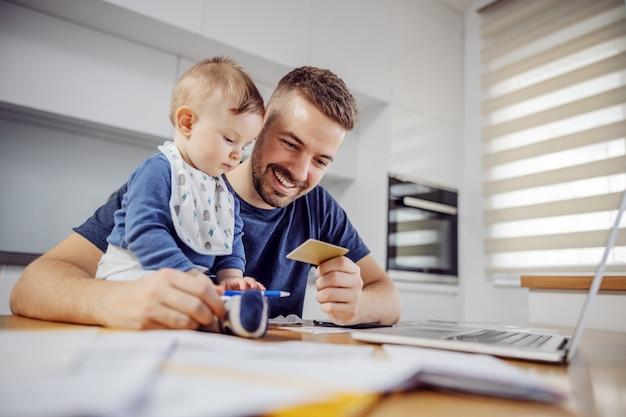 Jonge aantrekkelijke bebaarde vader zit aan de eettafel met zijn geliefde schattige zoon en rekeningen online betalen. zijn jongen houdt een pen vast en probeert hem te helpen.