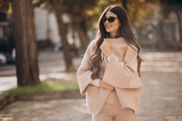 Jonge aantrekkelijke bedrijfsvrouw die in de straat loopt