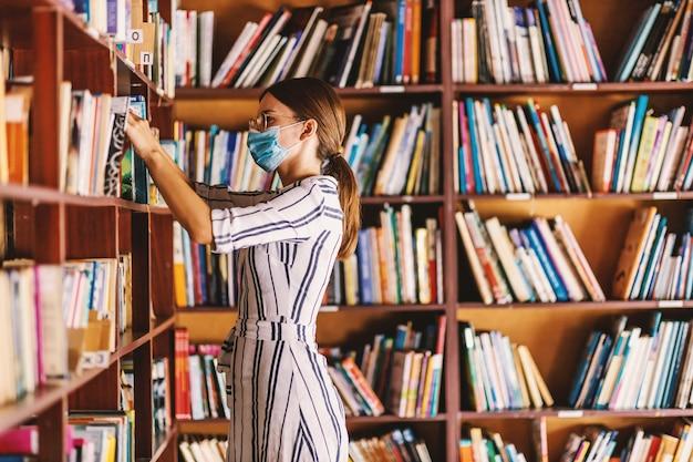 Jonge aantrekkelijke bibliothecaris met gezichtsmasker bij het zoeken naar een boek terwijl hij in de bibliotheek staat tijdens een coronavirus-pandemie.