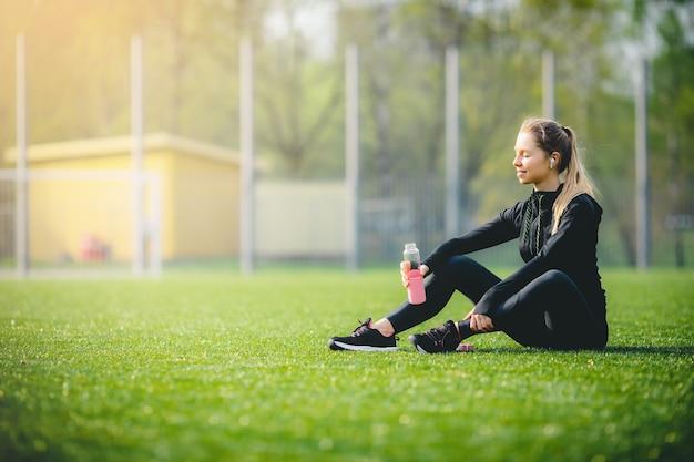 Jonge, aantrekkelijke blanke meid in een sportpak dat rust na het sporten, glimlachend en genietend van muziek