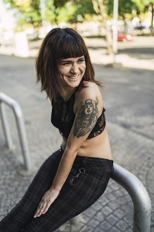 Jonge aantrekkelijke blanke vrouw met tatoeages in de straat
