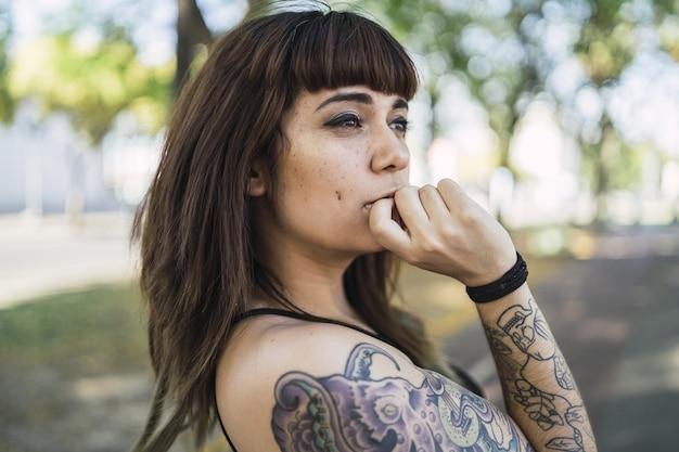 Jonge aantrekkelijke blanke vrouw met tatoeages staan ?? in het park en een schattig gezicht maken
