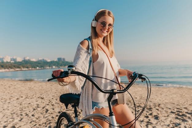 Jonge aantrekkelijke blonde glimlachende vrouw die op strand met fiets in hoofdtelefoons loopt die aan muziek in positieve gelukkige stemming luistert
