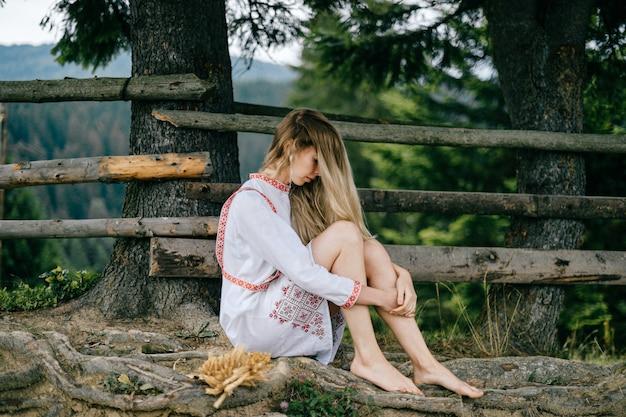 Jonge aantrekkelijke blonde meisje op blote voeten in witte jurk met ornament zitten in de buurt van houten hek buitenshuis