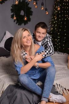 Jonge aantrekkelijke blonde moeder en haar zoon glimlachen en knuffelen in de kerstwoonkamer.