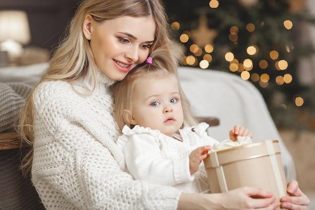 Jonge aantrekkelijke blonde moeder met haar kleine dochter in kerstmistijd. familie op kerstmis.