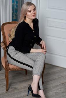 Jonge aantrekkelijke blonde vrouw die bedrijfskleren draagt die op een stoel zitten