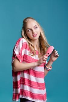 Jonge aantrekkelijke blonde vrouw die haar haar borstelt met roze kam op blauwe achtergrond
