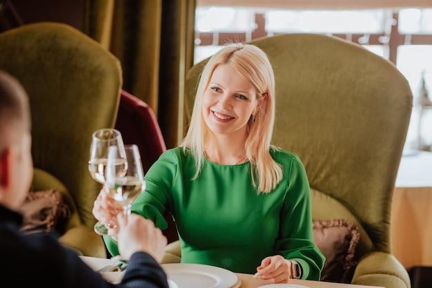 Jonge aantrekkelijke blonde vrouw in groene jurk tijd doorbrengen met man met glas witte wijn in het restaurant.