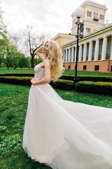 Jonge aantrekkelijke blondebruid met krullend haar dat in het park en het glimlachen loopt