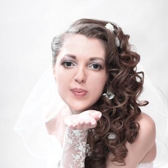 Jonge aantrekkelijke bruid in trouwjurk stuurt een kus