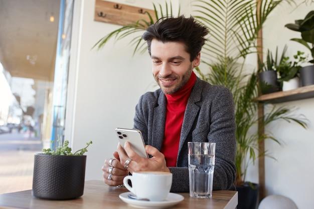 Jonge aantrekkelijke bruine haired ongeschoren mannelijke zit in stadscafé