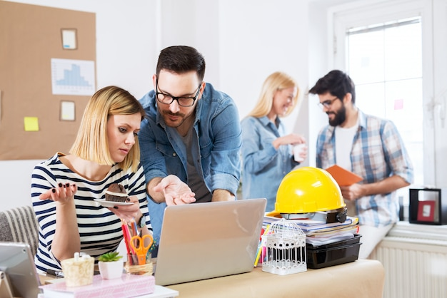 Jonge aantrekkelijke collega paar op zoek naar het oplossen van problemen op een laptop terwijl ze pauze hebben met andere collega's.
