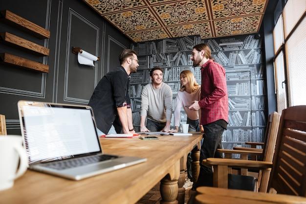 Jonge aantrekkelijke collega's staan in kantoor en naaiatelier