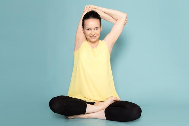 Jonge aantrekkelijke dame in geel overhemd en zwarte broek die yogahoudingen doen