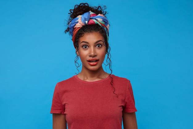 Jonge aantrekkelijke donkerharige dame met open ogen met veelkleurige hoofdband die verbaasd naar de voorkant kijkt terwijl ze over de blauwe muur staat in een casual t-shirt