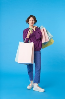 Jonge aantrekkelijke donkerharige vrouw met kort kapsel met veel boodschappentassen