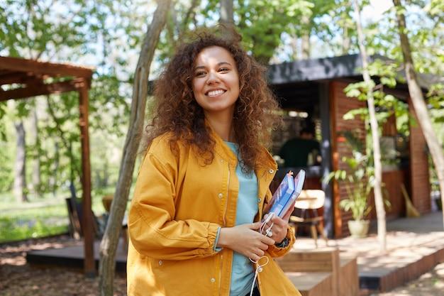 Jonge aantrekkelijke donkerhuidige gekrulde student dame op een caféterras wegkijken, gekleed in een gele jas, schoolboeken vasthouden, glimlacht breed, geniet van het weer.