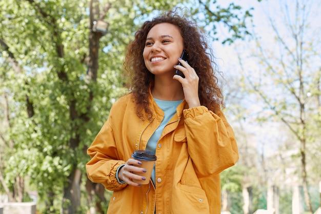 Jonge aantrekkelijke donkerhuidige krullende meisje breed glimlachend, praten aan de telefoon met zijn vriend, gekleed in een gele jas, koffie drinken, wandelen in het park bij mooi weer.