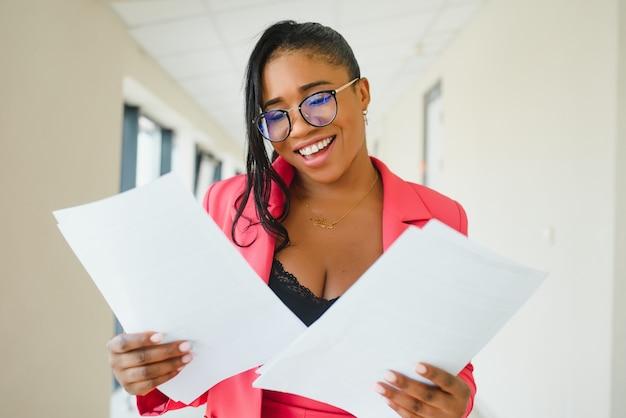 Jonge aantrekkelijke elegante afro-amerikaanse zakenvrouw in formele slijtage op kantoor hal.