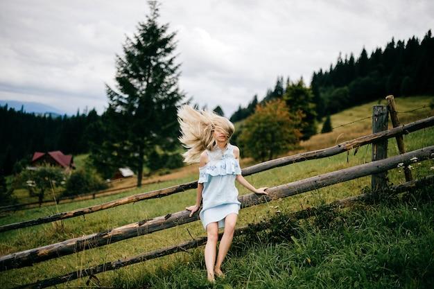 Jonge aantrekkelijke elegante blonde meisje in blauwe jurk met vliegend haar poseren in de buurt van hek op het platteland