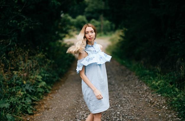 Jonge aantrekkelijke elegante blonde meisje in blauwe jurk poseren op de weg op het platteland