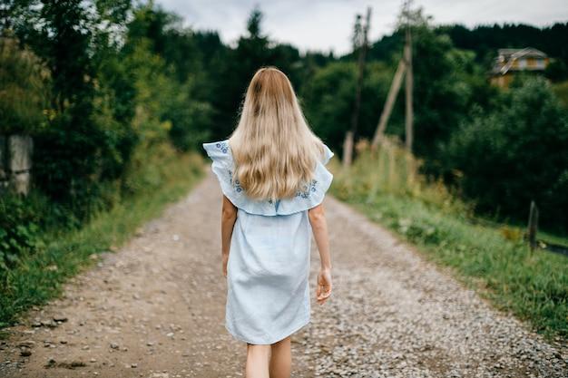 Jonge aantrekkelijke elegante blonde meisje in blauwe jurk poseren terug op de weg op het platteland