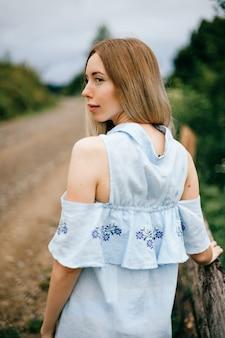 Jonge aantrekkelijke elegante blonde meisje in blauwe jurk poseren terug op het platteland