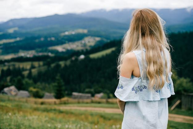 Jonge aantrekkelijke elegante blonde meisje in blauwe jurk poseren terug over schilderachtig landschap