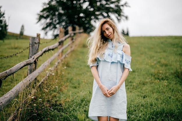 Jonge aantrekkelijke elegante blonde meisje in blauwe romantische jurk poseren in de buurt van hek op het platteland