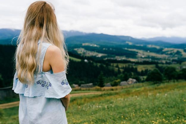 Jonge aantrekkelijke elegante blonde meisje in blauwe romantische jurk poseren terug over schilderachtig landschap