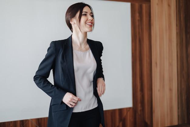 Jonge aantrekkelijke emotionele meisje in zakelijke stijl kleding op een effen witte achtergrond in een kantoor of publiek
