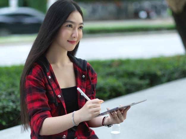 Jonge aantrekkelijke en mooie aziatische vrouw die op het stadsparkplein zit met tablet met styluspen