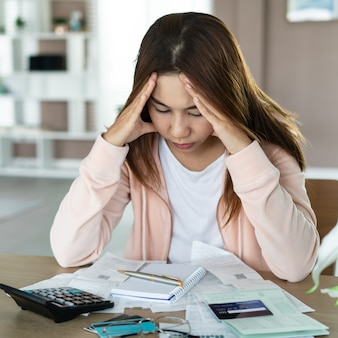 Jonge aantrekkelijke en wanhopige vrouw die aan spanning lijden die de binnenlandse rekeningen en facturen van de boekhoudingsadministratie ongerust maken en beklemtoond doen.